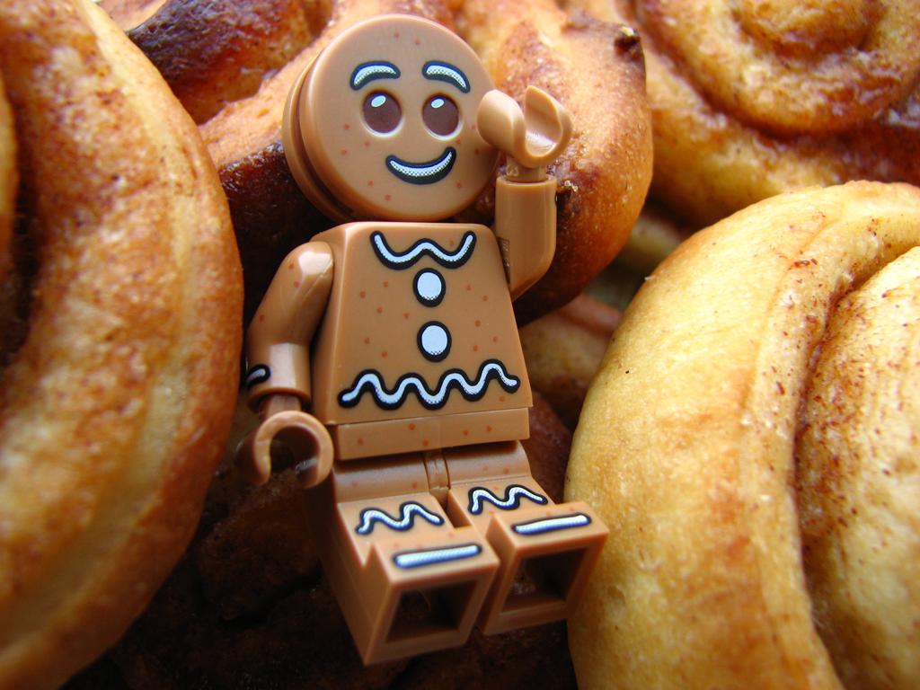 """Lego Minifigur """"Gingerbreadman"""" aus Sammelserie 11 liegt mit erhobenem Arm zwischen Zimtschnecken."""