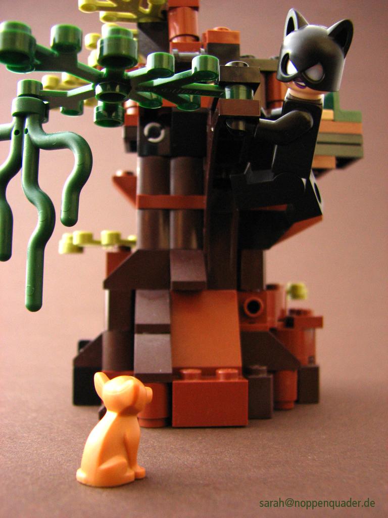 Lego Minifig Catwoman schwingt sich mit Blick auf einen Chihuahua auf den nächsten Baum