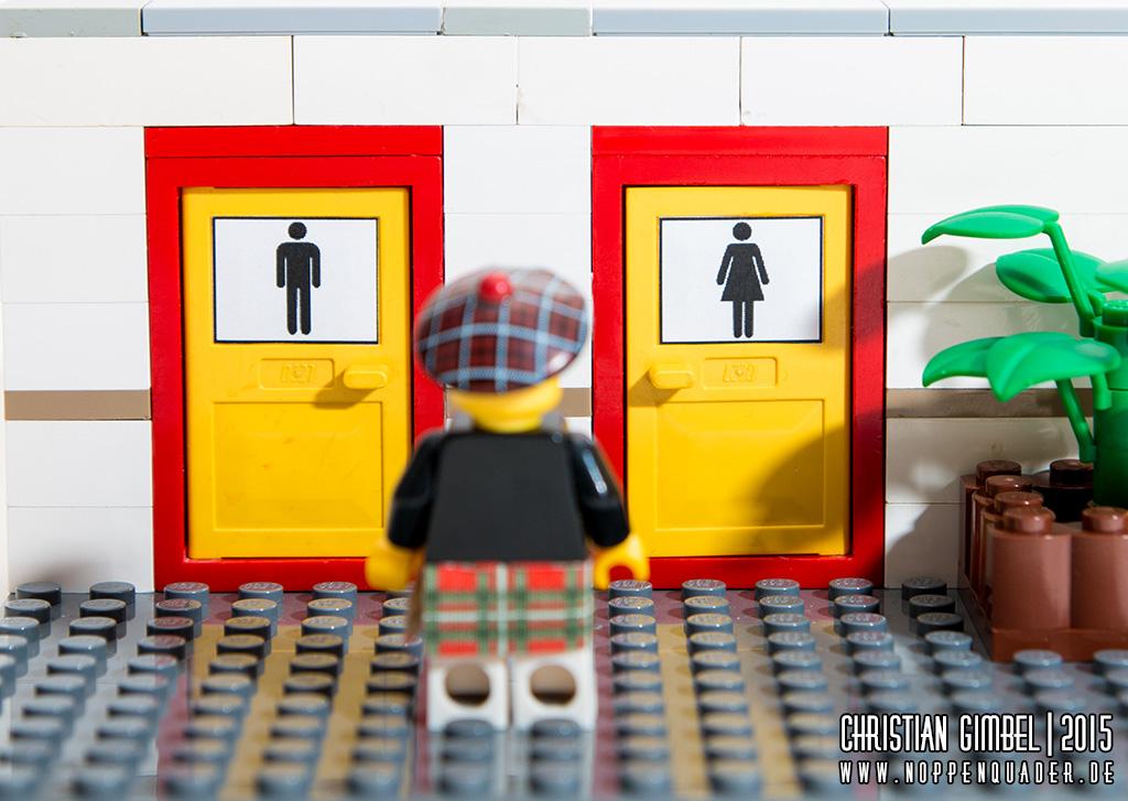 Noppenquader Lego Schotte vor einer Toilette kann sich nicht entscheiden, welche Tür richtig ist (Artikelbild)
